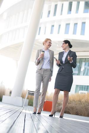 conversing: Full-length of businesswomen conversing outside office building LANG_EVOIMAGES
