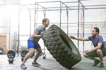 exercise weight: Man assisting at dedicated friend in flipping tire at crossfit gym
