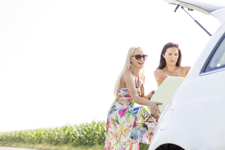 ���clear sky���: Happy female friends loading luggage in car trunk against clear sky