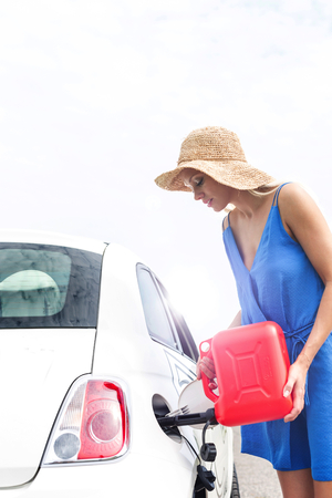 refueling: Woman refueling car against clear sky on sunny day