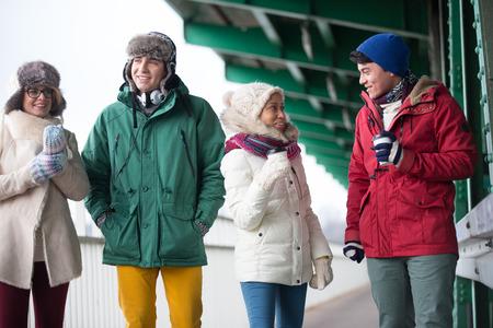 conversing: Multiethnic friends in winter wear conversing outdoors