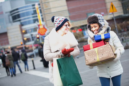 Happy women with gifts and shopping bags walking on city street during winter Stock Photo