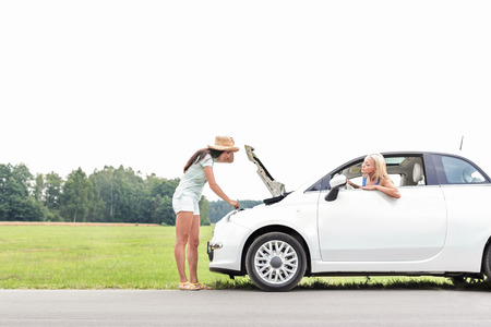 inconvenience: Woman looking at friend repairing broken down car on country road