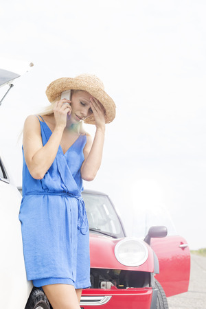 tensed: Tensed young woman using cell phone by broken down cars LANG_EVOIMAGES