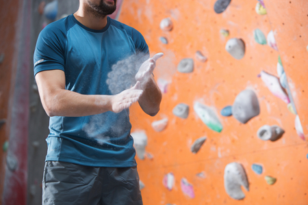 man climbing: Midsection of man dusting powder by climbing wall in crossfit gym