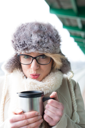 insulated drink container: Portrait of woman blowing coffee in insulated drink container during winter LANG_EVOIMAGES