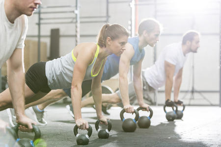 muscle training: Determined people doing pushups with kettlebells at crossfit gym LANG_EVOIMAGES