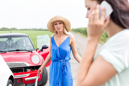 damaged cars: Angry woman looking at female using cell phone by damaged cars on road LANG_EVOIMAGES