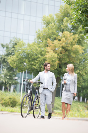 conversing: Businesspeople with bicycle conversing while walking on street