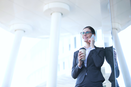 disposable cup: Businesswoman using cell phone while holding disposable cup outdoors