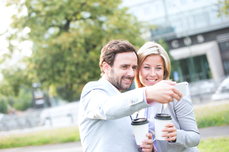 phone professional: Happy business couple taking selfie while holding disposable cups in city LANG_EVOIMAGES