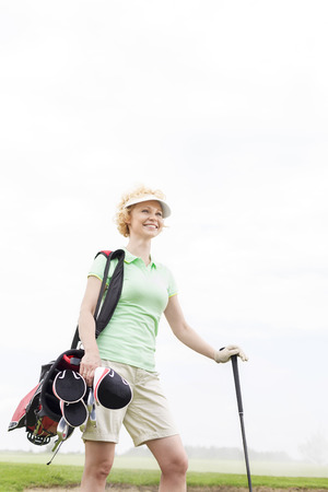 ���clear sky���: Low angle view of smiling female golfer standing against clear sky