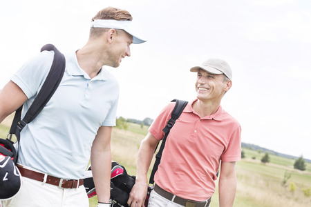 conversing: Happy male golfers conversing against clear sky LANG_EVOIMAGES