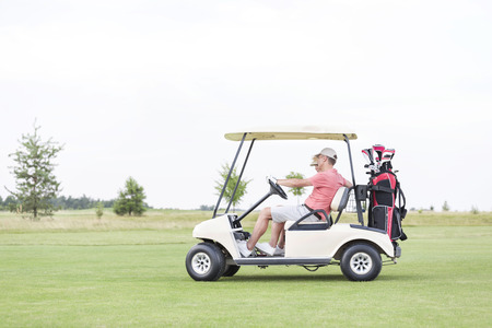 ���clear sky���: Side view of couple sitting in golf cart against clear sky