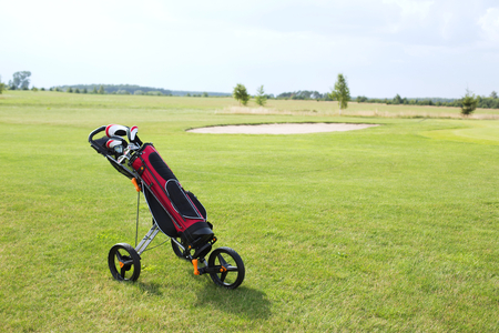 pushcart: Golf club bag on pushcart at golf course against sky LANG_EVOIMAGES