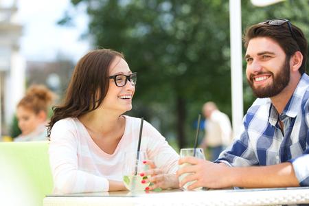 couple talking: Cheerful couple having mojito at sidewalk cafe