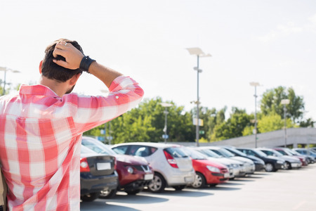 parking lot: Rear view of man with hand behind head standing on city street against clear sky