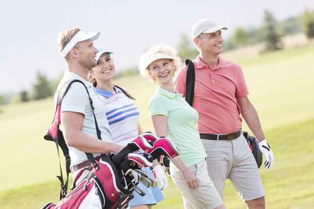 small group: Happy friends walking at golf course LANG_EVOIMAGES