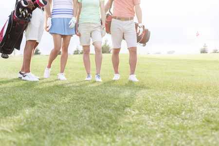 woman golf: Low section of friends standing at golf course