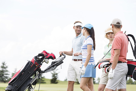 ���clear sky���: Friends communicating while walking at golf course against clear sky LANG_EVOIMAGES