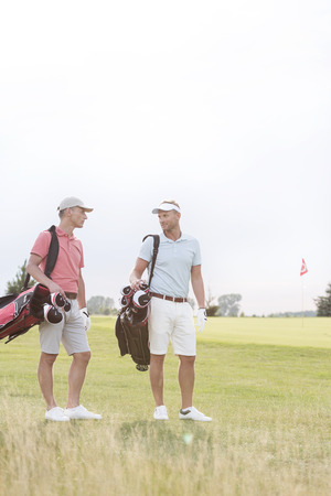 conversing: Full-length of men conversing at golf course against clear sky LANG_EVOIMAGES