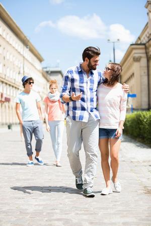 persona caminando: Pareja caminando en la calle con los amigos en el fondo