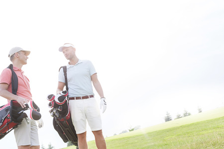 ���clear sky���: Male friends conversing at golf course against clear sky on sunny day