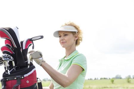 ���clear sky���: Female golfer with golf club bag against clear sky
