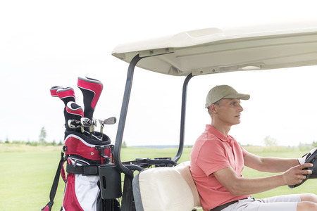 golf cart: Middle-aged man driving golf cart at course LANG_EVOIMAGES
