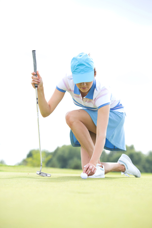 kneeling woman: Young woman placing ball while kneeling at golf course