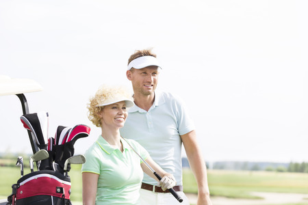���clear sky���: Smiling golfers standing at golf course against clear sky LANG_EVOIMAGES