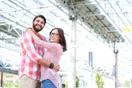 pareja abrazada: Pareja feliz mirando a otro lado mientras abraza edificio por fuera