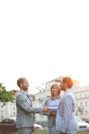 ���clear sky���: Happy businesspeople shaking hands in city against clear sky LANG_EVOIMAGES