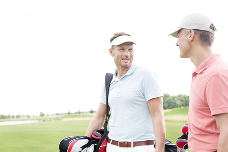 ���clear sky���: Happy golfer communicating with male friend against clear sky