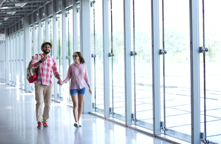 holding hands while walking: Full-length of couple holding hands while walking at covered passage