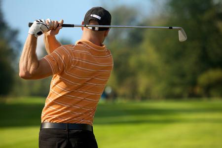 golf: Young man swinging golf club, rear view
