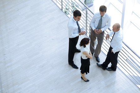 conversing: Businessmen and woman standing together by railing and conversing LANG_EVOIMAGES