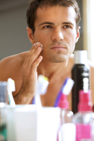 shaving cream: Reflection of young man in mirror applying shaving cream LANG_EVOIMAGES