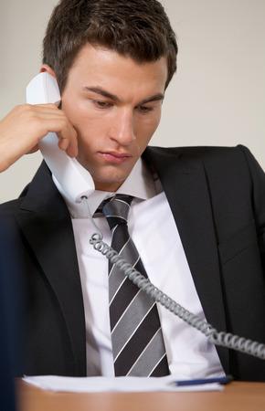 conversing: Businessman conversing on landline phone