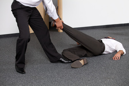dragging: Businessmen pulling colleagues leg at office