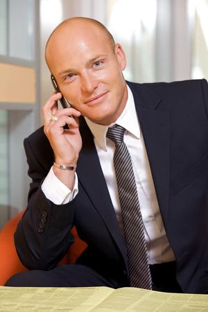 conversing: Businessman conversing on mobile phone, portrait