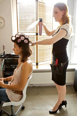 hairspray: Female hairdresser spraying hairspray in customers hair