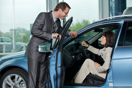 car salesperson: Car salesperson explaining car features to customer
