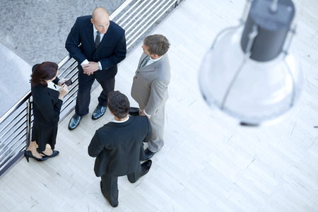 businesswoman standing: Businessmen and businesswoman standing together by railing