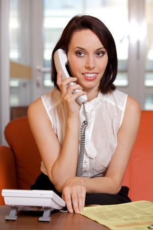raised eyebrow: Businesswoman conversing on landline phone