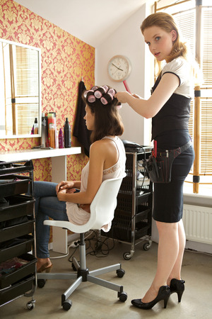 Female hairdresser adjusting curlers in young womans hair