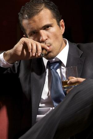hombre fumando puro: Retrato de joven hombre de fumar cigarros y copa que sostienen LANG_EVOIMAGES