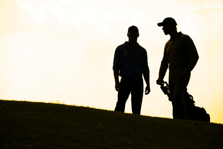 men standing: Silhouette of young men standing in golf course with trolley LANG_EVOIMAGES