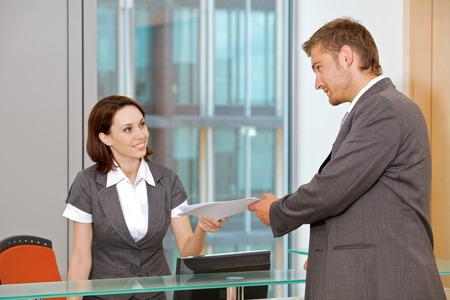 secretary desk: Young caucassian secretary assisting businessman LANG_EVOIMAGES