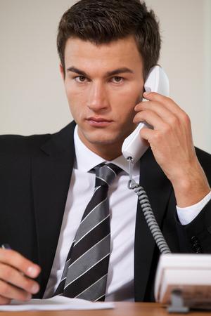 conversing: Businessman conversing on landline phone, portrait LANG_EVOIMAGES